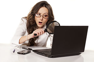 woman examining the cash discount program to find out if there is a catch. funny looking lady with her giant magnifying glass looking at the computer.